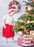 Portrait of a satisfied little girl next to the Christmas tree Stock Photos
