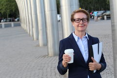 A portrait of a satisfied looking business woman with holding to go cup of coffee, documents folder and pen Stock Photo