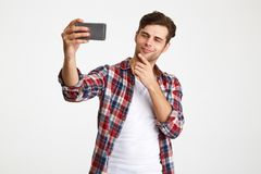 Portrait of a satisfied man taking a selfie while standing. Portrait of a satisfied charming man taking a selfie while standing isolated over white background royalty free stock images