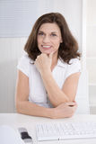 Portrait of satisfied older woman sitting at desk. Stock Photography