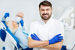 Portrait of satisfied stomatologist with crossed arms Stock Images
