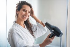 Optimistic female blowing wind on wet hair. Portrait of satisfied woman drying hair with technology. She flourishing arm and wearing bathrobe stock images