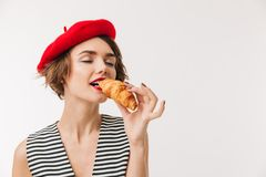 Portrait of a satisfied woman wearing beret eating croissant. Portrait of a satisfied woman wearing red beret eating croissant isolated over white background Royalty Free Stock Photo