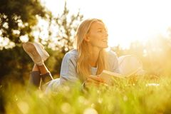 Portrait of a satisfied young girl with backpack. Laying on a grass at the park, reading a book Stock Photos