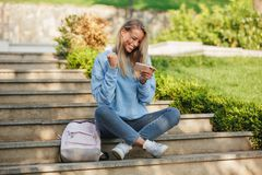 Portrait of a satisfied young girl student with backpack. Sitting on steps outdoors, playing games on mobile phone Stock Image
