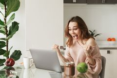 Portrait of a satisfied young woman sitting with laptop. Computer while having healthy breakfast at the table at home Royalty Free Stock Image