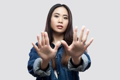 Portrait of scared beautiful brunette asian young woman in casual blue denim jacket with makeup standing with hand blocking and. Looking at camera. indoor royalty free stock image