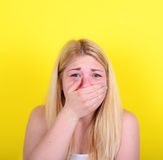 Portrait of scared girl against yellow background Stock Photography