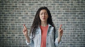 Portrait of scared girl making praying hands gesture on brick wall background stock video footage