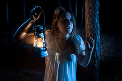 Portrait of scared woman lost in forest lighting up the way with Stock Image