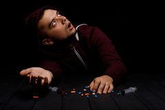 A young addict male is depressed and scared on a black background. A human with a lot of narcotic drugs on a table. A portrait of a scared young addict man with Stock Photo