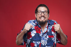 Portrait of a scared young man in Hawaiian shirt against red bac Stock Photography