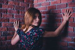Portrait of a scared young woman. Scared young woman standing in corner of brick wall and looking at camera royalty free stock photos