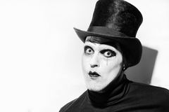 Portrait of a scary angry mime. Wearing a tall hat on white background.  Theatrical make-up Stock Photography