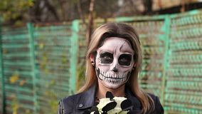 Scary girl with make-up on a halloween with a bouquet of black flowers. Portrait of a scary girl with make-up on a halloween in the form of a skull with a stock video