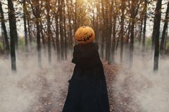 Portrait of a scary Jack-lantern with a pumpkin on his head. Halloween legend. Dressed in black coat. Autumn forest stock photo