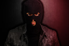 Portrait of a scary thief. On a dark background royalty free stock image