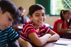Portrait Of School Boy Looking At Camera In Class. Young people and education. Group of hispanic students in class at school during lesson. Happy boy smiling and Royalty Free Stock Photo