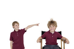 Portrait of school boy smiling while friend pointing at him over white background Stock Photos