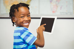 Portrait of school boy using a digital tablet in classroom Royalty Free Stock Photos