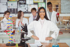 Portrait of school girl standing with hand on hip in laboratory. At school Royalty Free Stock Photo