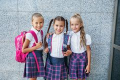 Portrait of school kids with backpack after school. Beginning of lessons. First day of fall. Pupils of primary school. Girls with backpacks near building Stock Image