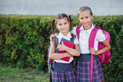 Portrait of school kids with backpack and books after school. Beginning of lessons. First day of fall. Pupils of primary school. Girls with backpacks and books Stock Photography