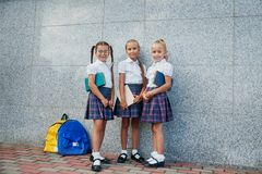 Portrait of school kids with backpack and books after school. Beginning of lessons. First day of fall. Pupils of primary school. Girls with backpacks and books Royalty Free Stock Photos