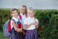 Portrait of school kids with backpack and books after school. Beginning of lessons. First day of fall. Pupils of primary school. Girls with backpacks and books Royalty Free Stock Photo