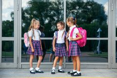 Portrait of school kids with backpack going after school. Beginning of lessons. First day of fall. Pupils of primary school. Girls with backpacks near building Stock Photos