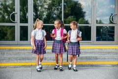 Portrait of school kids with backpack going after school. Beginning of lessons. First day of fall. Pupils of primary school. Girls with backpacks near building Royalty Free Stock Images