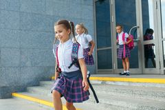 Pupils of primary school. Girls with backpacks near building outdoors. Beginning of lessons. First day of fall. Portrait of school kids with backpack running Stock Photography