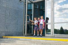 Pupils of primary school. Girls with backpacks near building outdoors. Beginning of lessons. First day of fall. Portrait of school kids with backpack running Stock Photo
