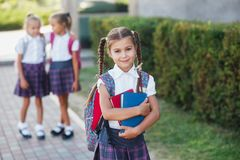 Portrait of school kids with backpack after school. Beginning of lessons. First day of fall. Pupils of primary school. Girls with backpacks near building Royalty Free Stock Photography