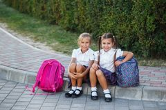 Portrait of school kids with backpack after school. Beginning of lessons. First day of fall. Pupils of primary school. Girls with backpacks near building Royalty Free Stock Image