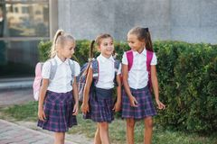 Portrait of school kids with backpack after school. Beginning of lessons. First day of fall. Pupils of primary school. Girls with backpacks near building Stock Photography
