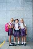 Portrait of school kids with backpack after school. Beginning of lessons. First day of fall. Pupils of primary school. Girls with backpacks near building Stock Images