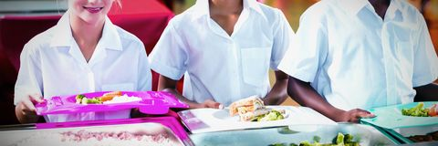 Portrait of school kids having lunch during break time royalty free stock photos