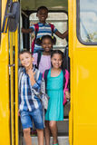 Portrait of school kids looking from bus. Portrait of smiling school kids looking from bus Stock Photo
