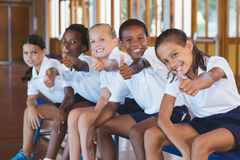Portrait of school kids showing thumbs up in basketball court Stock Photo