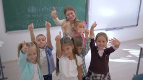 Portrait of school kids with teacher showing thumbs up and then applaud in classroom on background of board at school stock video footage