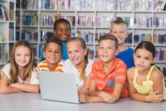 Portrait of school kids using laptop in library Stock Photography