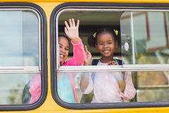 Portrait of school kids waving hand from bus Royalty Free Stock Photos