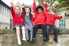 Portrait Of School Pupils Sitting On Wall Together Royalty Free Stock Images