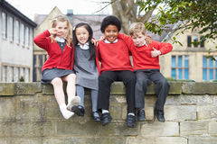 Portrait Of School Pupils Sitting On Wall Together Stock Photo