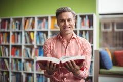 Portrait of school teacher holding book in library. Portrait of smiling school teacher holding book in library at school Stock Image