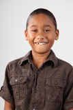Portrait of schoolboy 9 with huge toothy smile. Young boy, 9, with big toothy smile to camera in studio against white background - Canon 5D MKII Royalty Free Stock Image
