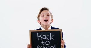 Schoolboy holding chalkboard with back to school text stock video footage