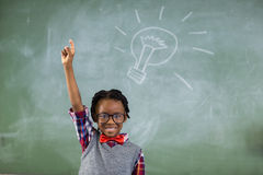Portrait of schoolboy raising his hand against chalkboard Royalty Free Stock Images