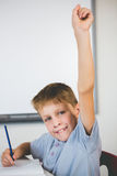 Portrait of schoolboy raising his hand in classroom Stock Images